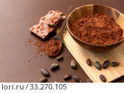 Купить «chocolate with hazelnuts, cocoa beans and powder», фото № 33270105, снято 1 февраля 2019 г. (c) Syda Productions / Фотобанк Лори