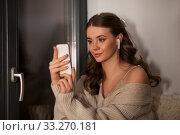 Купить «woman with smartphone and earphones at home», фото № 33270181, снято 19 января 2020 г. (c) Syda Productions / Фотобанк Лори
