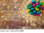 chocolate eggs in foil wrappers in straw nest. Стоковое фото, фотограф Syda Productions / Фотобанк Лори