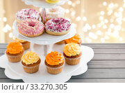 glazed donuts, cupcakes with frosting on stand. Стоковое фото, фотограф Syda Productions / Фотобанк Лори