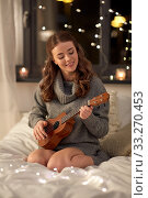 Купить «happy young woman playing guitar in bed at home», фото № 33270453, снято 19 января 2020 г. (c) Syda Productions / Фотобанк Лори