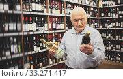 Купить «Portrait of male customer selecting wine in supermarket», видеоролик № 33271417, снято 25 мая 2020 г. (c) Яков Филимонов / Фотобанк Лори