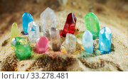 Multicolored crystal quartz sticks of gems protrude from the sand. Стоковое фото, фотограф Федонников Никита Александрович / Фотобанк Лори