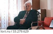 Купить «Elderly grandfather - grandfather is sitting in a wheelchair, lifts up his jacket sleeve and looking at watch», видеоролик № 33279629, снято 31 мая 2020 г. (c) Константин Шишкин / Фотобанк Лори