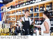 Seller helping woman customer with bottle of wine. Стоковое фото, фотограф Яков Филимонов / Фотобанк Лори