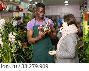 Seller offering gift flower arrangement to female. Стоковое фото, фотограф Яков Филимонов / Фотобанк Лори
