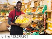 Купить «Seller showing lemons at farmer market», фото № 33279961, снято 13 февраля 2020 г. (c) Яков Филимонов / Фотобанк Лори