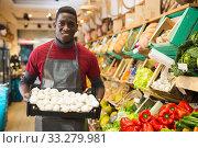 Greengrocery owner offering mushrooms for sale. Стоковое фото, фотограф Яков Филимонов / Фотобанк Лори