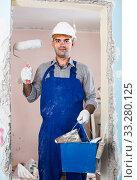 adult man repairer working with roller in uniform, gloves and helmet. Стоковое фото, фотограф Яков Филимонов / Фотобанк Лори