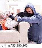 Купить «The armed man assaulting young woman at home», фото № 33280265, снято 15 декабря 2017 г. (c) Elnur / Фотобанк Лори