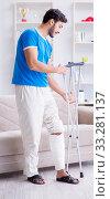 Купить «Injured young man recovering at home», фото № 33281137, снято 27 июля 2017 г. (c) Elnur / Фотобанк Лори