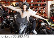 smiling couple having fun at motorcycle salon after buying new bike. Стоковое фото, фотограф Яков Филимонов / Фотобанк Лори