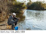 Купить «Man fishing with rods on river», фото № 33283189, снято 27 января 2019 г. (c) Яков Филимонов / Фотобанк Лори