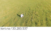 Купить «UHD 4k aerial view. Low orbital flight over businessman sitting on green grass with notebook pad at field», видеоролик № 33283537, снято 13 марта 2017 г. (c) Александр Маркин / Фотобанк Лори