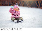 Girl shod in figure skates, sits on ice on a skating rink and waves a hand. Стоковое фото, фотограф Екатерина Кузнецова / Фотобанк Лори
