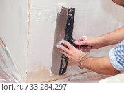 Купить «Repair of the living quarters. Putty interior walls with a wide metal spatula», фото № 33284297, снято 6 июня 2020 г. (c) Екатерина Кузнецова / Фотобанк Лори