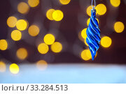 Купить «The Christmas Christmas-tree decoration, blue icicle hangs against the background of yellow a bokeh», фото № 33284513, снято 10 августа 2018 г. (c) Екатерина Кузнецова / Фотобанк Лори