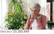 Купить «happy senior woman with cup of tea at home», видеоролик № 33285849, снято 19 января 2020 г. (c) Syda Productions / Фотобанк Лори