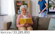 old woman reading book and housekeeper at home. Стоковое видео, видеограф Syda Productions / Фотобанк Лори