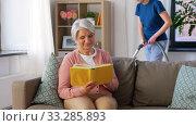 Купить «old woman reading book and housekeeper at home», видеоролик № 33285893, снято 19 января 2020 г. (c) Syda Productions / Фотобанк Лори
