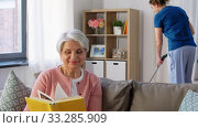 Купить «old woman reading book and housekeeper at home», видеоролик № 33285909, снято 19 января 2020 г. (c) Syda Productions / Фотобанк Лори
