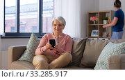 Купить «old woman with smartphone and housekeeper at home», видеоролик № 33285917, снято 19 января 2020 г. (c) Syda Productions / Фотобанк Лори