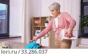 Купить «senior woman picking clothes for laundry at home», видеоролик № 33286037, снято 19 января 2020 г. (c) Syda Productions / Фотобанк Лори