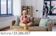 Купить «old woman with smartphone and housekeeper at home», видеоролик № 33286057, снято 19 января 2020 г. (c) Syda Productions / Фотобанк Лори