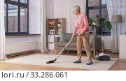 Купить «senior woman with vacuum cleaner cleaning at home», видеоролик № 33286061, снято 19 января 2020 г. (c) Syda Productions / Фотобанк Лори