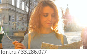 Woman is lost in old European city looking at a map and searching for direction early in the morning on ancient square. Стоковое видео, видеограф Ольга Балынская / Фотобанк Лори