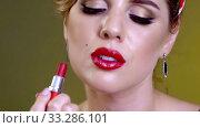 Lipstick in woman hand who paints red lips. Стоковое видео, видеограф Gennadiy Poznyakov / Фотобанк Лори