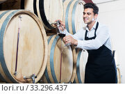 Seller pouring wine in cellar. Стоковое фото, фотограф Яков Филимонов / Фотобанк Лори