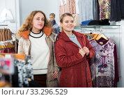 Купить «Women posing in overcoats in clothing boutique», фото № 33296529, снято 6 декабря 2018 г. (c) Яков Филимонов / Фотобанк Лори