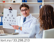 Купить «Doctor optician with letter chart conducting an eye test check», фото № 33298213, снято 30 марта 2017 г. (c) Elnur / Фотобанк Лори