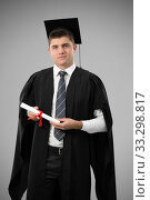 Купить «Portrait of a Caucasian male student holding a certificate graduating», фото № 33298817, снято 3 июля 2019 г. (c) Wavebreak Media / Фотобанк Лори