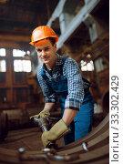 Купить «Worker removes scale from metal workpieces», фото № 33302429, снято 31 января 2020 г. (c) Tryapitsyn Sergiy / Фотобанк Лори