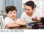 Купить «Boy smiling while mother reprimanding him», фото № 33302553, снято 28 марта 2019 г. (c) Яков Филимонов / Фотобанк Лори