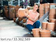 Купить «Young woman customer looking decorative clay pot for garden», фото № 33302589, снято 6 апреля 2020 г. (c) Яков Филимонов / Фотобанк Лори
