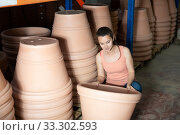 Купить «Young woman customer holding big decorative clay pot for garden», фото № 33302593, снято 6 апреля 2020 г. (c) Яков Филимонов / Фотобанк Лори