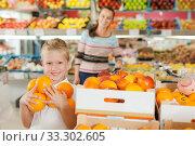 Купить «kid with woman choosing oranges», фото № 33302605, снято 20 апреля 2019 г. (c) Яков Филимонов / Фотобанк Лори