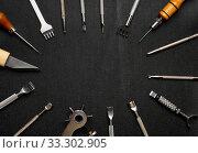 Leather crafting DIY tools lies on natural black leather. Стоковое фото, фотограф Бражников Андрей / Фотобанк Лори