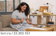 Купить «woman with papers and calculator at home», видеоролик № 33303161, снято 24 февраля 2020 г. (c) Syda Productions / Фотобанк Лори