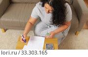 Купить «woman with money, papers and calculator at home», видеоролик № 33303165, снято 26 февраля 2020 г. (c) Syda Productions / Фотобанк Лори