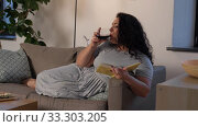 woman reading book and drinking red wine at home. Стоковое видео, видеограф Syda Productions / Фотобанк Лори