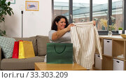Купить «happy young woman with shopping bag at home», видеоролик № 33303209, снято 24 февраля 2020 г. (c) Syda Productions / Фотобанк Лори