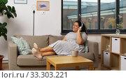 Купить «woman in headphones listens to music on smartphone», видеоролик № 33303221, снято 24 февраля 2020 г. (c) Syda Productions / Фотобанк Лори