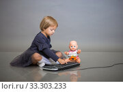 The little girl in a gray dress sits with a doll on a gray background and plays with the keyboard from the computer. Стоковое фото, фотограф Екатерина Кузнецова / Фотобанк Лори