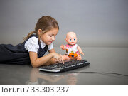 The little girl the schoolgirl on a gray background plays with the keyboard from the computer and a doll. Стоковое фото, фотограф Екатерина Кузнецова / Фотобанк Лори
