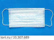 Купить «Medical surgical face mask on blue background. World pandemic insurance, airborne diseases, SARS, influenza», фото № 33307689, снято 5 марта 2020 г. (c) А. А. Пирагис / Фотобанк Лори