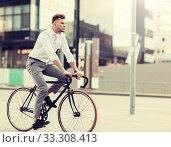 Купить «man with headphones riding bicycle on city street», фото № 33308413, снято 21 августа 2016 г. (c) Syda Productions / Фотобанк Лори